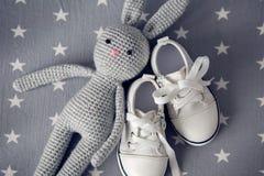 灰色编织了玩具兔子,并且儿童` s白色鞋子在灰色背景 库存照片