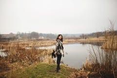 灰色羊毛衫和黑帽会议微笑和姿势的少女在湖的岸 免版税库存照片