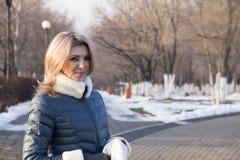 灰色背景的女孩在室外的冬天 免版税库存照片