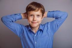 灰色背景的少年男孩 库存图片