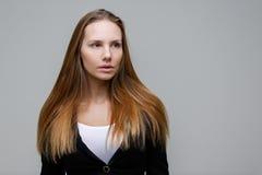 灰色背景的白肤金发的妇女 免版税图库摄影