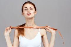灰色背景的美丽的少妇,画象,饮食,健身,体育,丢失的重量 免版税图库摄影