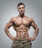 灰色背景的肌肉运动员爱好健美者人 库存照片