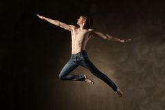 灰色背景的年轻和时髦的现代舞蹈家 免版税库存图片