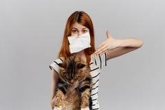 灰色背景的年轻美丽的妇女拿着一只猫,对宠物的过敏 图库摄影