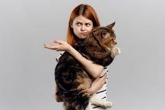灰色背景的年轻美丽的妇女拿着一只猫,情感,宠物 免版税库存照片
