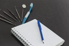 灰色表面上的牙齿仪器与白色笔记本 免版税图库摄影