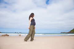 灰色衬衣怀孕走在海洋旁边 库存照片