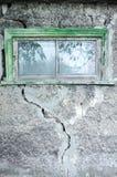 灰色装饰膏药纹理与一个大裂缝和窗口的 库存图片