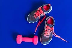灰色运动鞋变粉红色在蓝色背景的鞋带哑铃 库存照片