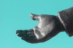 灰色金属雕象手伸出反对土耳其玉色背景 免版税库存图片