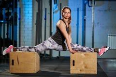 灰色绑腿的美丽的女孩下来坐在健身房的麻线 十字架适合 免版税库存照片