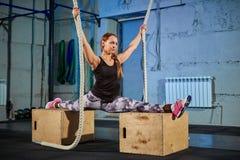 灰色绑腿的美丽的女孩下来坐在健身房的麻线 十字架适合 库存照片