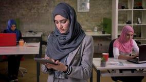 灰色hijab的逗人喜爱的阿拉伯女性swwiping她的gerey片剂并且看presicely它,当站立在其他附近时 股票录像