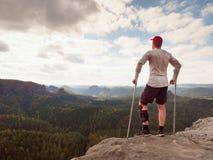 灰色T恤杉的远足者,被修理的医学拐杖和腿固定达到的山峰 图库摄影