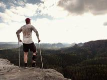 灰色T恤杉的远足者,被修理的医学拐杖和腿固定达到的山峰 免版税图库摄影