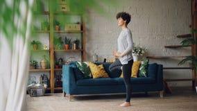 灵活和坚强的少妇在家训练做站立在与被举的胳膊的一腿维护的平衡的瑜伽 影视素材