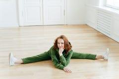 灵活性,健身和舒展概念 可爱的红头发人女性做腿分裂,舒展腿,佩带绿色sweatsuit, 免版税库存照片
