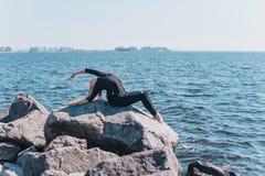 灵活的体操运动员在Th的一块石头做在后面的偏折 免版税库存图片