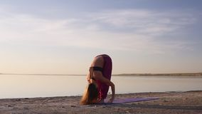 灵活的健康女孩实践瑜伽海滩 舒展 Sealine日出慢动作 股票录像