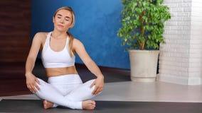 灵活的坐在现代瑜伽演播室的莲花坐的少女放松的转动的身体 股票视频