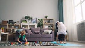 灵活的女子实践的瑜伽在家,当她的使用与块时的年轻儿子 股票录像