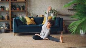 灵活的女孩今后在供以座位的位置弯曲并且扭转她的身体享受瑜伽的和活动坐地板  影视素材