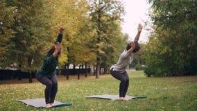 灵活的女孩在公园实践站立椅子的位置在瑜伽席子和移动的身体和头 美好的秋天 股票视频