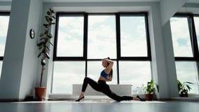 灵活的女孩在慢动作实践瑜伽并且执行新月形asana 影视素材
