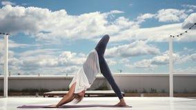 灵活的妇女做在慢动作的瑜伽在云彩和天空蔚蓝背景中  股票录像