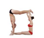 灵活的信奉瑜伽者套用信函'O'与他们的身体 库存图片