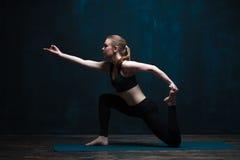 年轻灵活的女子实践的瑜伽户内 免版税库存照片