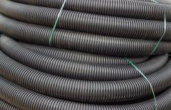黑灵活的输送管道尼龙管子背景卷  免版税库存图片