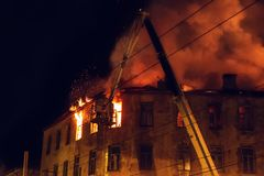 灼烧的大厦房子在晚上,屋顶在火火焰的和烟,起重机的消防队员熄灭火用从水管的水 免版税库存照片