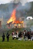 灼烧的房子 在战场的战士行军 库存照片