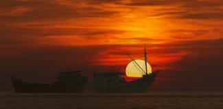 灼烧的橙色天空和小船 库存照片