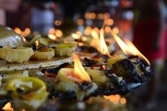 灼烧的油印度寺庙蜡烛:在一片被折叠的叶子倾吐的油,投入了灯芯被点燃和闪烁的火 库存图片