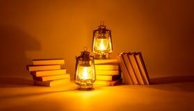 灼烧的煤油灯和书,光的概念魔术 免版税库存图片