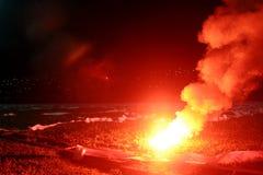 灼烧的红色火光,火焰,橄榄球小流氓 足球迷打开了光和烟幕弹在橄榄球球场 灼烧的红色fl 免版税库存图片