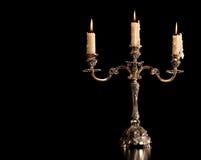 灼烧的老蜡烛葡萄酒银古铜烛台 查出的黑色背景 免版税库存图片