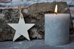 灼烧的蜡烛、星和木头在混凝土宿营 免版税库存照片