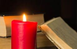 灼烧的蜡烛和一些旧书 免版税库存照片
