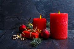 灼烧的蜡烛和在有圣诞节球的一个小礼物盒旁边 免版税库存照片