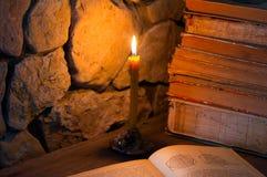 灼烧的蜡烛和旧书 库存图片