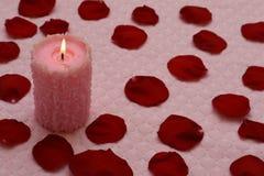 灼烧的蜡烛和红色玫瑰花瓣 免版税库存图片