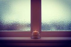 灼烧的蜡烛和结霜的窗口在冬天微明下 库存图片