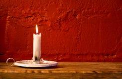 灼烧的蜡烛红色墙壁 库存图片