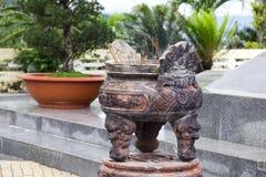 灼烧的香火在有寺庙的一个特别装饰的碗黏附在背景 免版税库存图片