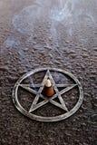 灼烧的香火在灰色金属五角星形的中心在板岩backg的 图库摄影