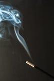 灼烧的香火黏附与烟在黑暗的背景 免版税库存照片